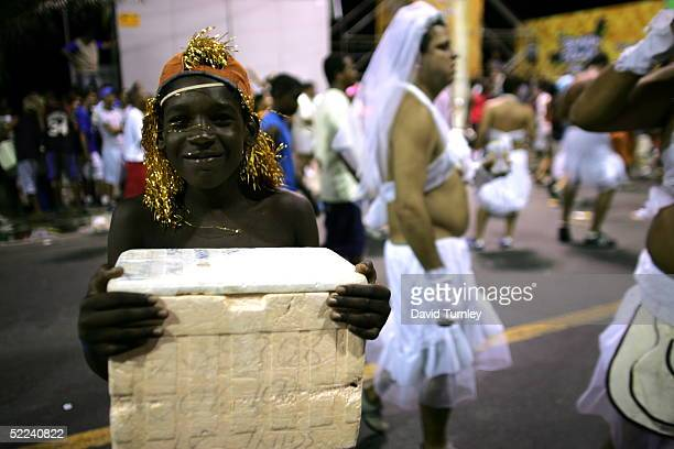 A young boy sells soft drinks as people dance through the streets during Carnival on February 5 2005 in Salvador Brazil Centuries of slave trade with...