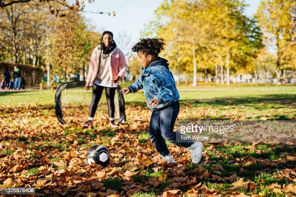 young boy shooting while playing soccer with family - shooting at goal stock pictures, royalty-free photos & images