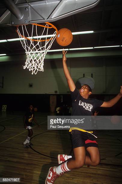 A young boy shoots a layup in a gym at the Chicago Commons Association a West Side center based in the Henry Horner Homes Chicago Illinois late 1980s