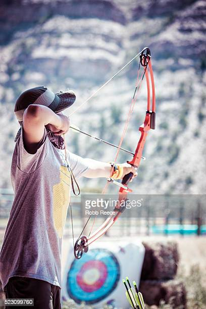a young boy shoots an arrow at an archery range in colorado - robb reece stock-fotos und bilder