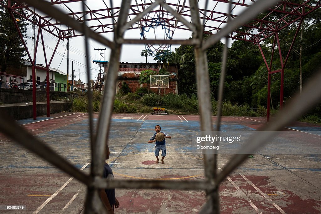 A young boy shoots baskets on a court during a visit by Henrique Capriles, governor of the state of Miranda and a former presidential candidate in the last two elections, not poctured, in Barlovento, Venezuela, on Saturday, May 10, 2014. Capriles, one of the leaders of the Democratic Unity Roundtable, known as MUD, an alliance which opposes Venezuelan President Nicolas Maduro, said talks with the government scheduled for May 8 were canceled because they 'haven't produced any result up to now.' Photographer: Meridith Kohut/Bloomberg via Getty Images