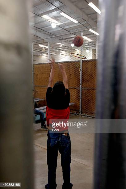 A young boy shoots the basketball at a makeshift hoop in a holding cell where hundreds of mostly Central American immigrant children are being...