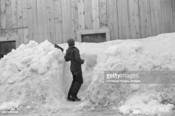 Young Boy Shoveling Snow from Barn Window after Heavy Snowfall near Woodstock Vermont USA Marion Post Wolcott for Farm Security Administration April...