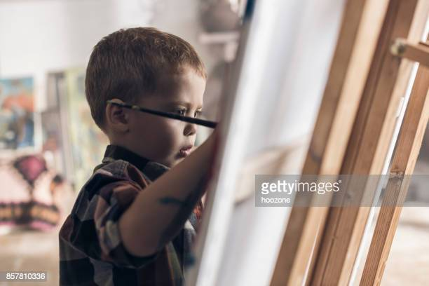 Young boy showing creative aspirations in an atelier