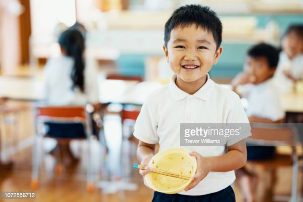 young boy showing his empty bowl after eating school lunch at preschool - 少年 ストックフォトと画像