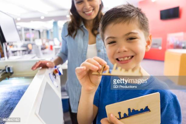 young boy shows off object from 3d printer - 3d mom son stock photos and pictures