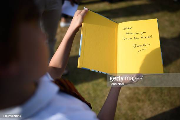 A young boy shows off the personal message from Foreign Secretary Jeremy Hunt in his politics for children textbook after Mr Hunt spoke to members of...