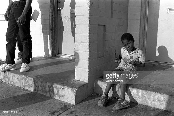 A young boy shows off what he has learned from his elder brothers hanging out on the stoop of his family's apartment The Grape Street Watts Crips are...