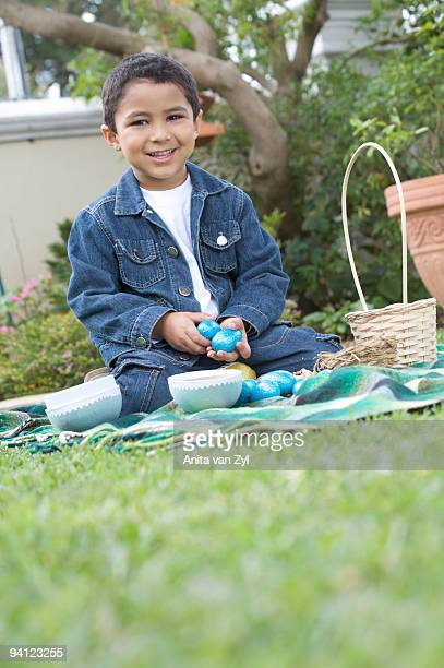 Young boy siiting the yard with easter eggs, South Africa
