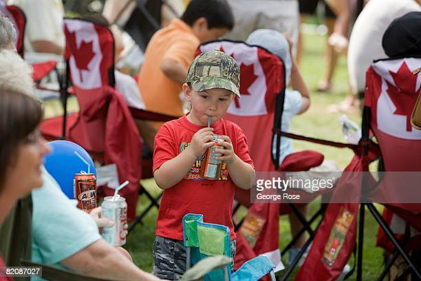 A young boy sips soda from a can during Canada Day festivities in this 2008 Penticton British Columbia Canada summer photo Canada Day is the Canadian...