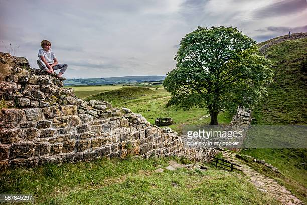 A young boy siting on Hadrians Wall