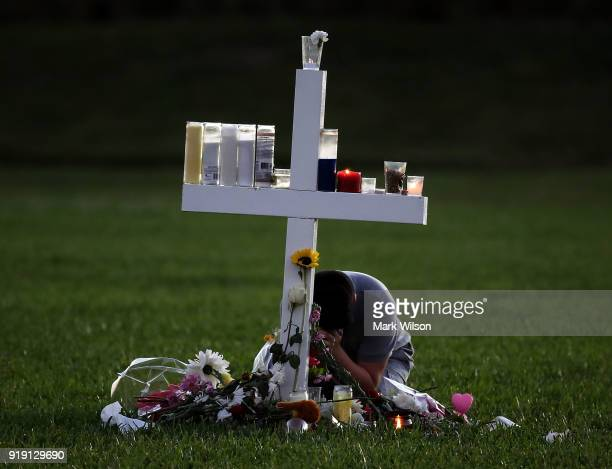 A young boy sits a memorial cross that honors victims of the mass shooting at Marjory Stoneman Douglas High School at Pine Trail Park on February 16...