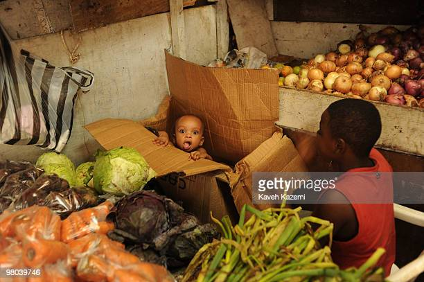 BUENAVENTURA COLOMBIA DECEMBER 30 2009 A young boy sits amidst grocery playing around with his elder brother in a cardboard box in a stand where his...