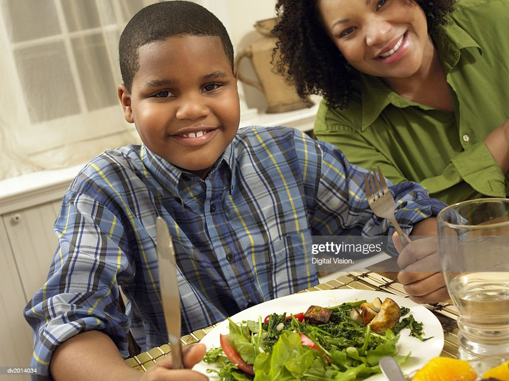 Young Boy Sits at a Table Next to His Mother, With a Plate of Salad : Stock Photo