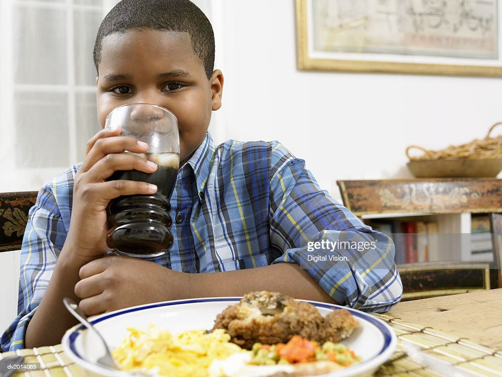 Young Boy Sits at a Table With a Plate of Food, Drinking a Glass of Cola : Stock Photo