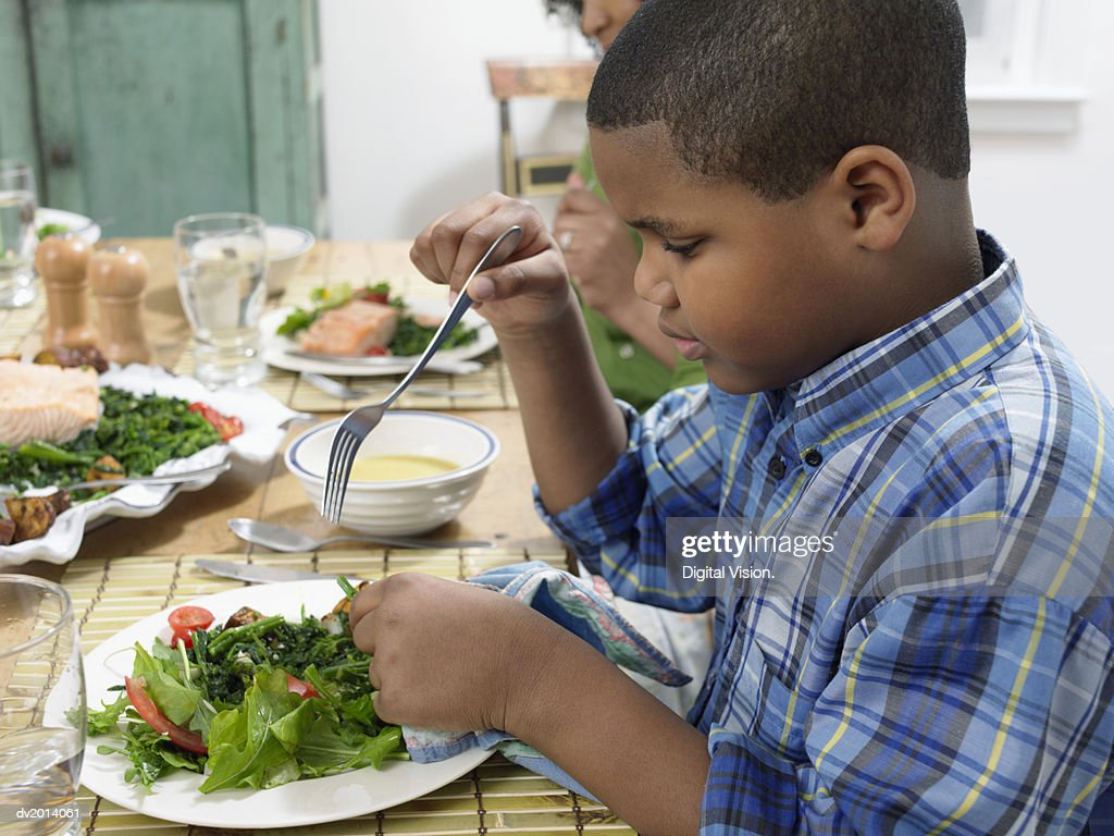 Young Boy Sits at a Table With a Plate of Salad, Holding a Fork : Stock Photo