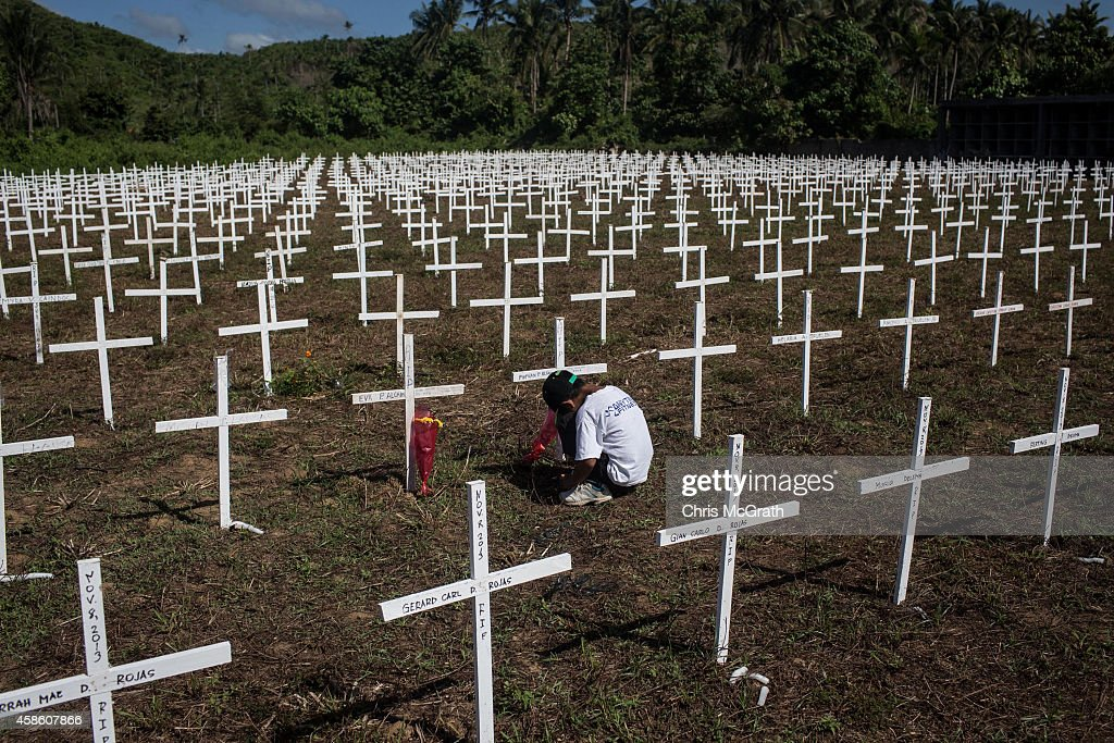 TACLOBAN, LEYTE, PHILIPPINES - NOVEMBER 08: A young boy sits at the cross of a loved one at the mass grave on the grounds of the Holy Cross Memorial Garden on November 8, 2014 in Tacloban, Leyte, Philippines. Residents and typhoon survivors from across the central Philippines attended memorial services and visited mass graves honouring those who lost their lives one year ago when Typhoon Haiyan, the strongest typhoon ever to make landfall swept across the region, leaving more than 6000 dead and many more homeless.