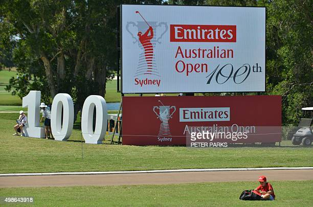 A young boy sits at the side of the fairway in front of a sign for the Australian Open golf tournament at the Australian Golf Club in Sydney on...