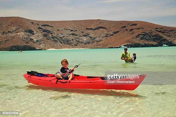 a young boy sits in a red boat by the shore while a father and son play out in the water at los islotes national marine park espiritu santo island; la paz baja california mexico - son la stock pictures, royalty-free photos & images