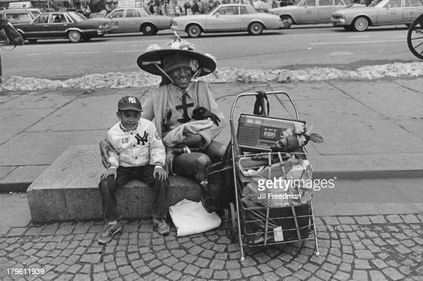 A young boy sits next to a homeless man cradling a rabbit on 5th Avenue New York City 1982