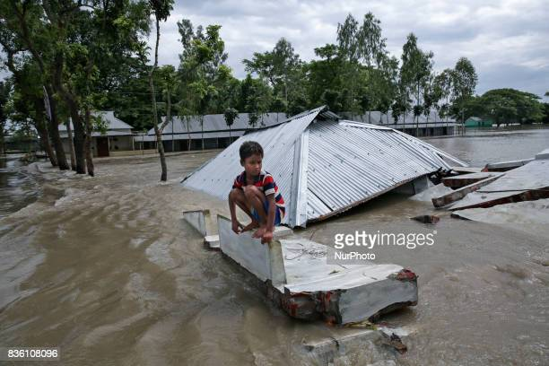 Young boy sits on a debris caused by the flood in Jamalpur Bangladesh on 19 August 2017