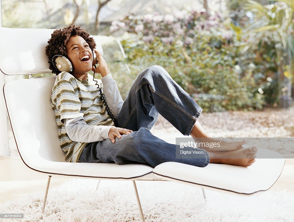 Young Boy Sits on a Lounger Chair Listening to Music on Headphones and Laughing : Stock Photo