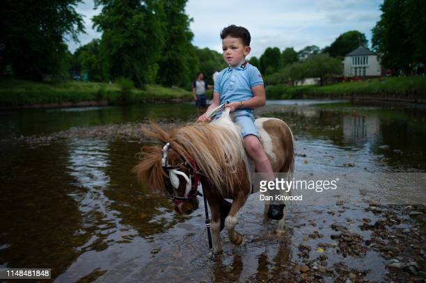 Young boy sits on a miniature Pony in the River Eden during the annual Appleby Horse Fair on June 07, 2019 in Appleby-in-Westmorland, England. The...