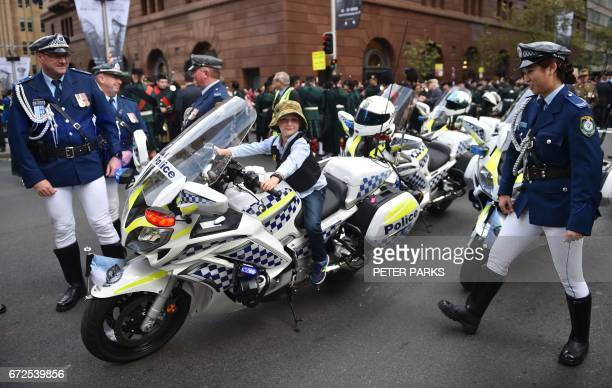 A young boy sits on a police motorcycle before the start of the Anzac Day parade in Sydney on April 25 2017 Ceremonies are held annually on April 25...
