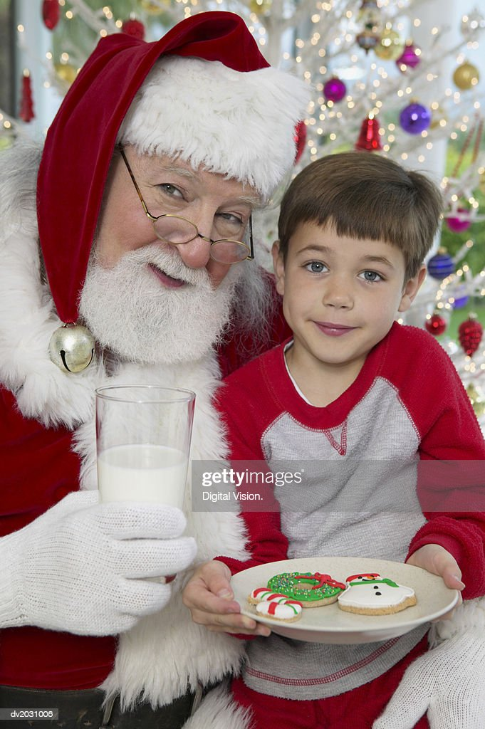 Young Boy Sits on Father Christmas' Lap With a Plate of Cookies and a Glass of Milk : Stock Photo