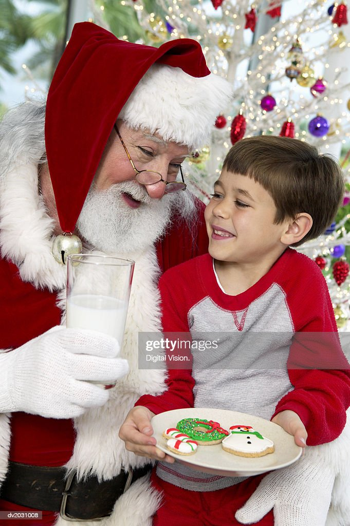Young Boy Sits on Father Christmas' Lap With a Plate of Cookies and a Glass of Milk, Laughing : Stock Photo