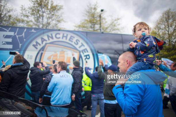 Young boy sits on his father's shoulders as the team bus arrives before the Premier League match between Manchester City and Everton at Etihad...