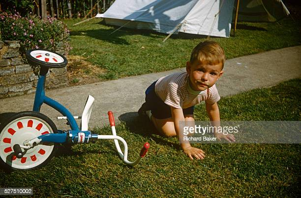 A young boy sits on the lawn after falling from his tricycle on a summer's day in the family garden in the early nineteen sixties Sitting on his...