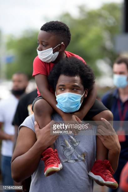 A young boy sits on the shoulder's of a man both wearing facemasks during a Justice for George Floyd event in Houston Texas on May 30 after George...