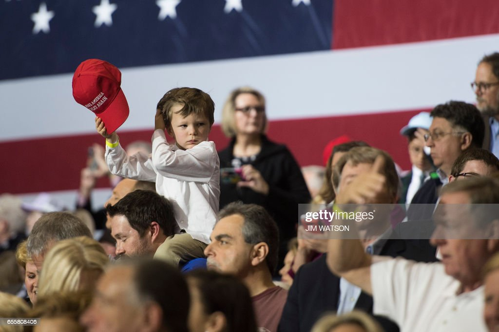 A young boy sits on the shoulders of a supporter as US President Donald Trump arrives to speak at a 'Make America Great Again' rally at the Kentucky Exposition Center in Louisville, Kentucky, March 20, 2017. /