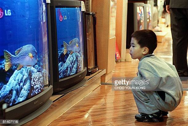 A young boy sits watching a locallymade TV as he waits for his parents to choose a set in a department store in Seoul 22 September 1999 The boy's...