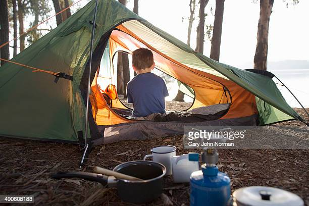 Young boy sitting alone in tent