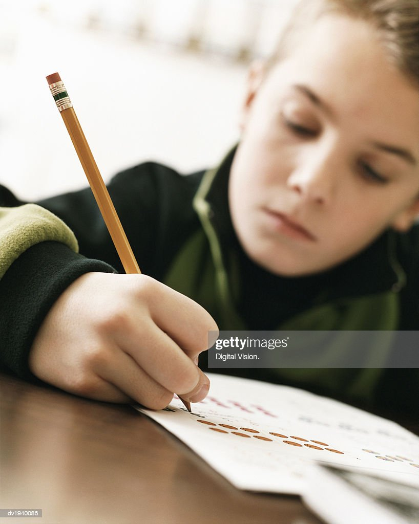 Young Boy Sitting at a Desk in a Classroom and Writing in His Exercise Book : Stock Photo