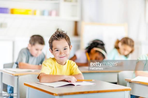 kleiner junge sitzt an seinem schreibtisch in der schule - 6 7 jahre stock-fotos und bilder