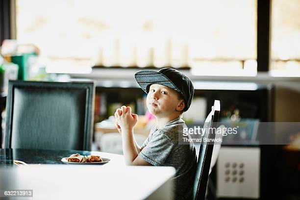 Young boy sitting at table in home eating lunch