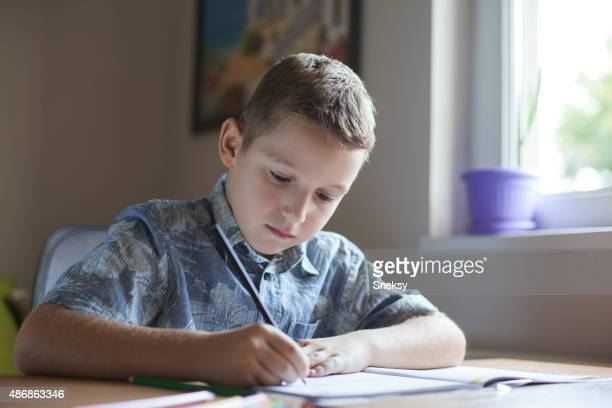 Young boy sitting at the table doing his school homework.