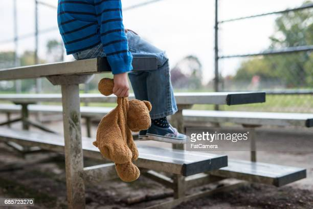 Young boy sitting by himself on on bleachers.