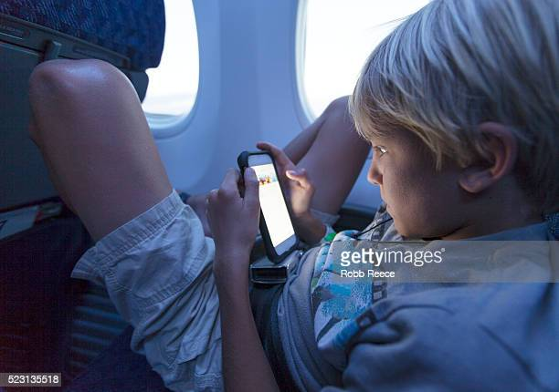a young boy sitting in an airplane looking at a smartphone - robb reece stockfoto's en -beelden