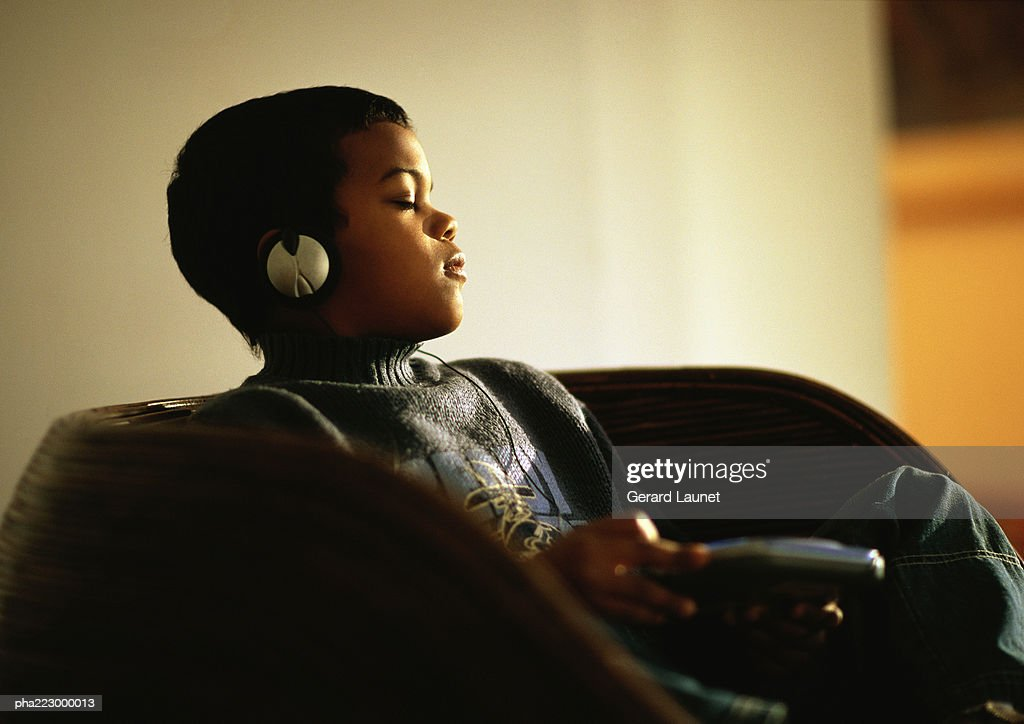 Young boy sitting in chair listening to music through headphones with eyes closed. : Stockfoto
