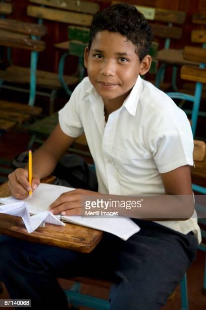 young boy sitting in classroom  - américa central fotografías e imágenes de stock