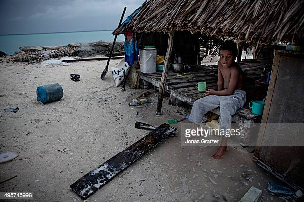 A young boy sitting in his family's house whilst the sea water floods the underside of the house The people of Kiribati are under pressure to...