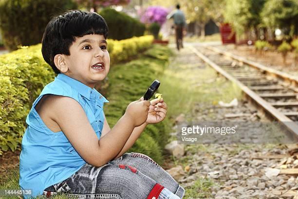 Young boy sitting near railway tracks