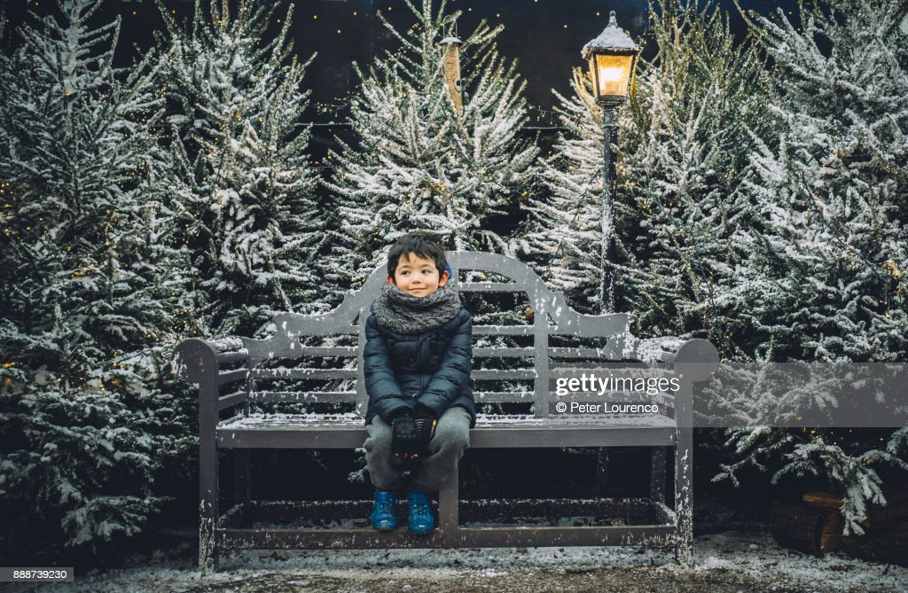 Young boy sitting on a bench in a festive Christmas setting. : Stock Photo