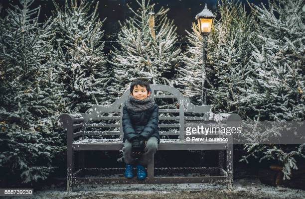 Young boy sitting on a bench in a festive Christmas setting.