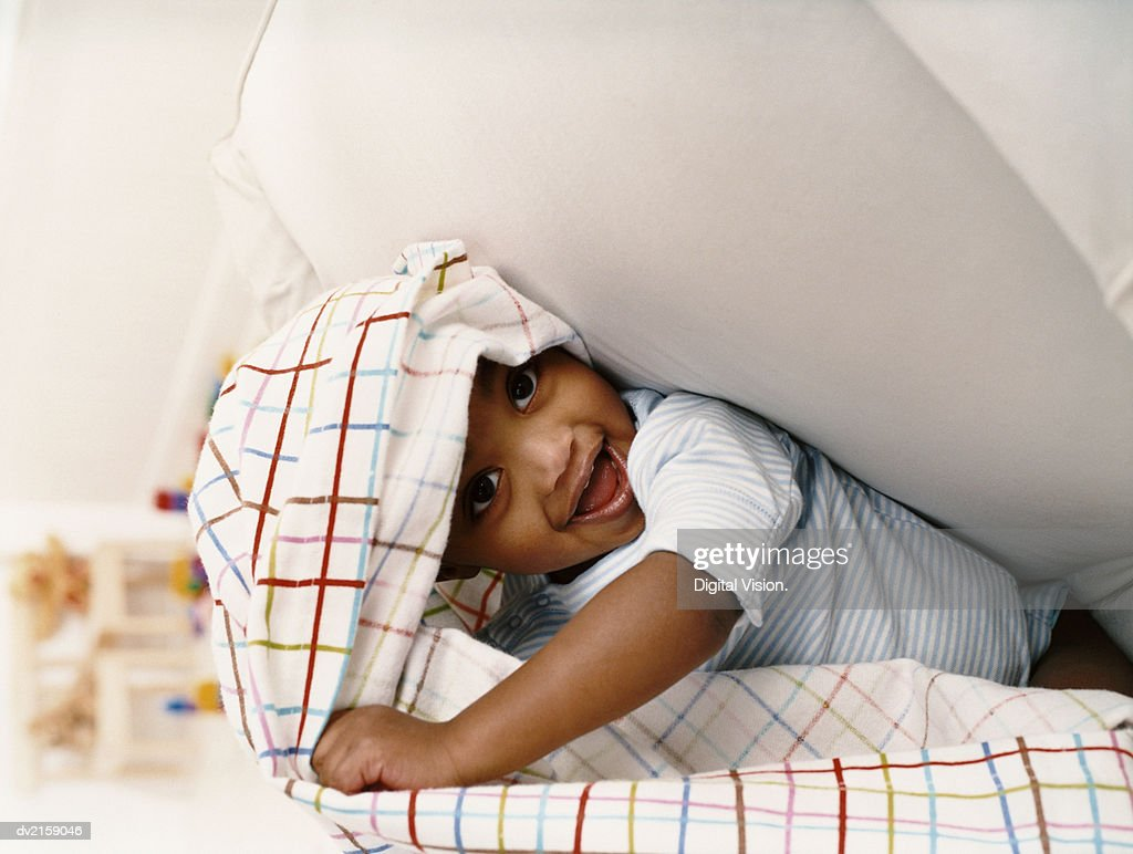 Young Boy Sitting on a Chair and Playing Under a Sheet : Stock Photo