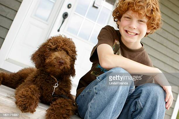 A young boy sitting on a porch with a brown dog
